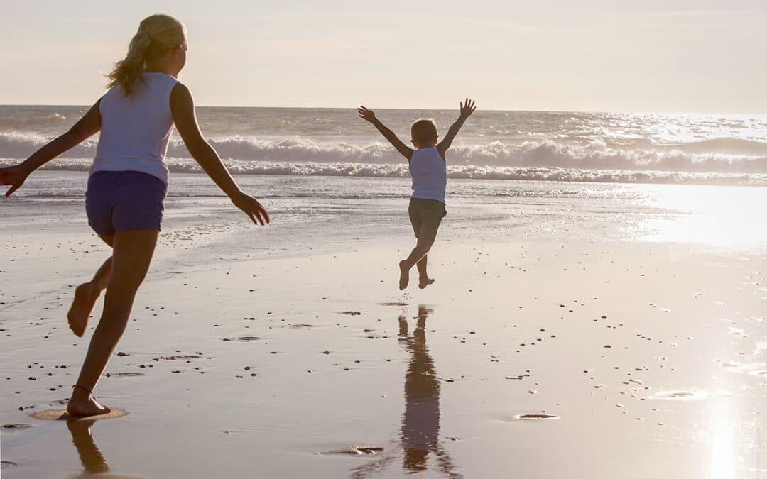 Twee kinderen rennen richting de zee op een strand van de Atlantische Kust in Frankrijk.