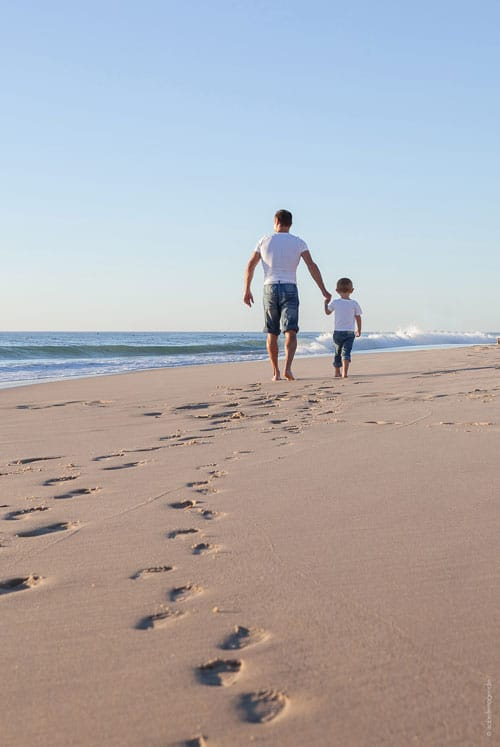 Een man en een jongen laten voetstappen achter in het strand aan de Atlantische Kust van Frankrijk.
